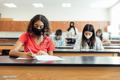 High school students and teenagers go back to school in the classroom at their high school. They are required to wear face masks and practice social distancing during the COVID-19 pandemic. They value their education and are excited to be in school. Image taken in Utah, USA.
