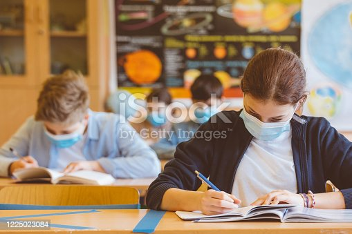 High school students at school, wearing N95 Face masks. Sitting in a classroom and writing lessons.