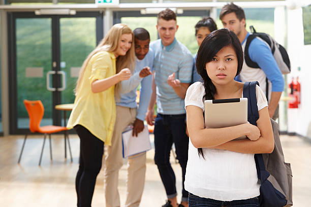 High school students bully a nearby female student stock photo