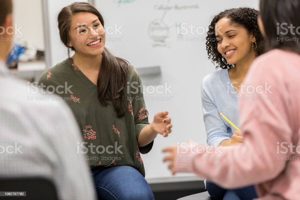 Hispanic female high school student brainstorms with a group of...
