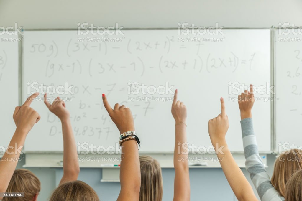 High school students in classroom raising hands stock photo