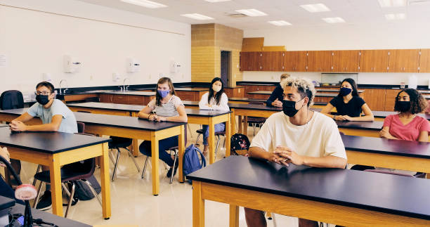 High School Students In Classroom Wearing Protective Face Mask stock photo