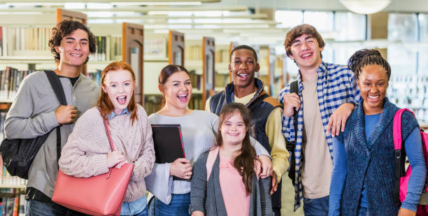 High school students in library, girl with down syndrome A multi-ethnic group of seven high school students, 15 to 17 years old, standing together in a library, smiling and looking at the camera. The girl in the middle has down syndrome. teenagers only stock pictures, royalty-free photos & images