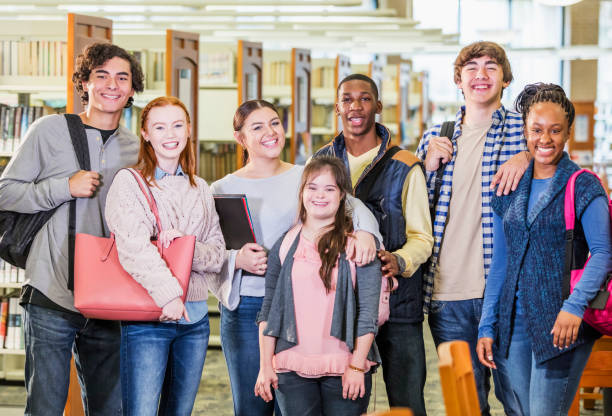 High school students in library, girl with down syndrome A multi-ethnic group of seven high school students, 15 to 17 years old, standing together in a library, smiling and looking at the camera. The girl in the middle has down syndrome. learning difficulty stock pictures, royalty-free photos & images