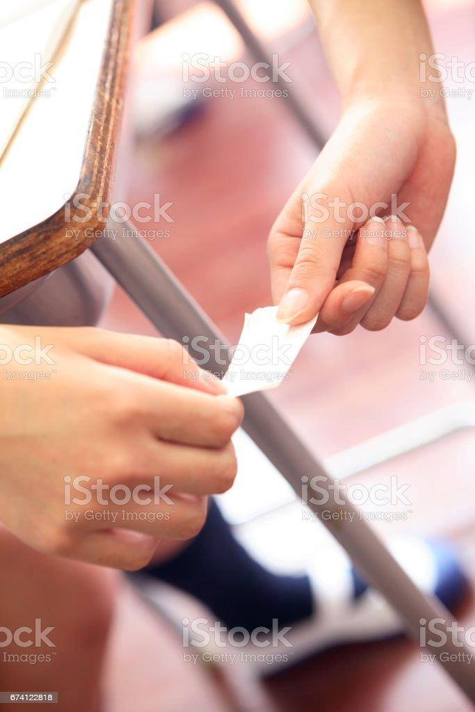 高中學生傳紙條交給 免版稅 stock photo