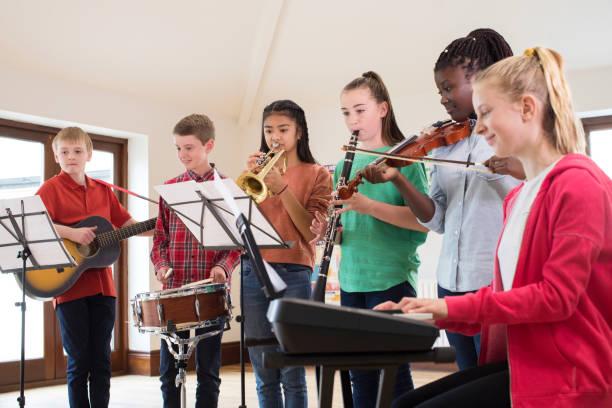 middelbare scholieren spelen school orkest samen - music stockfoto's en -beelden