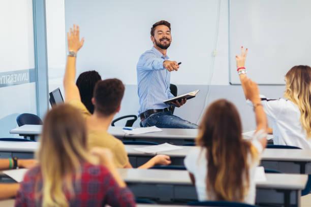 estudantes do ensino médio que levantam as mãos em uma classe - professor - fotografias e filmes do acervo
