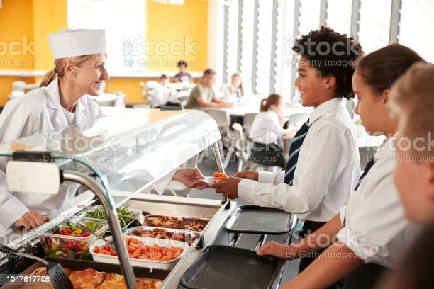 High school students wearing uniform being served food in canteen picture id1047617708?b=1&k=6&m=1047617708&s=612x612&h=orajudzeirrvxu5ldeobultvzvhcfqc21 4archtk7k=