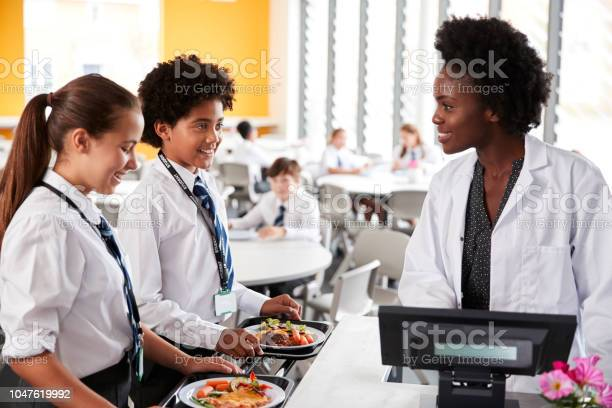 High school students wearing uniform paying for meal in cafeteria picture id1047619992?b=1&k=6&m=1047619992&s=612x612&h=bgwvzjdnms6iwzmxavbdl y52gunoiswneb4z7zjcga=