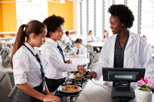 high school students wearing uniform paying for meal in cafeteria - banchi scuola foto e immagini stock