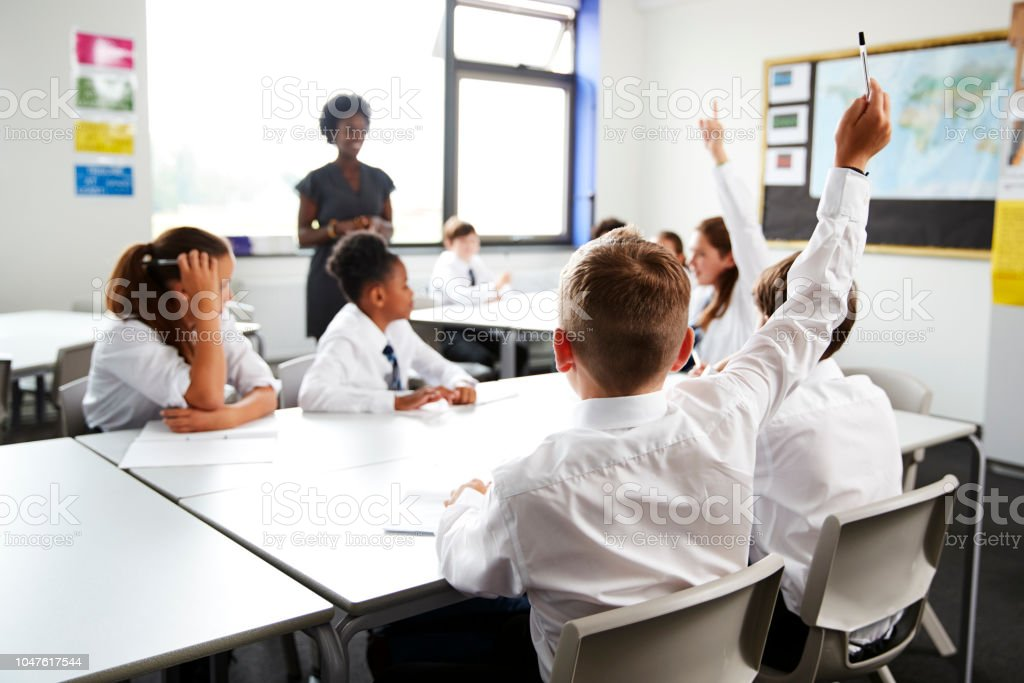 High School Students Wearing Uniform Raising Hands To Answer Question Set By Teacher In Classroom stock photo