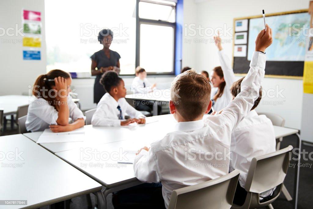 SchülerInnen und Schüler tragen einheitliche Erhöhung der Hände um die Frage zu beantworten festgelegten Lehrer im Klassenzimmer – Foto