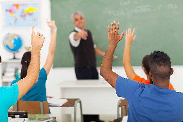 high school students with hands up in classroom stock photo