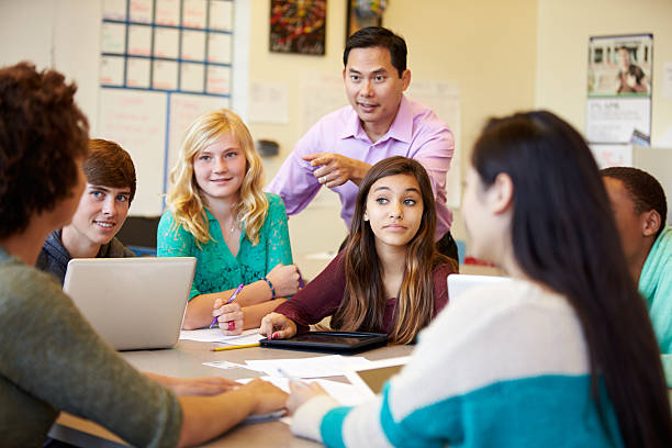 high school students with teacher in class using laptops - high school teacher stock pictures, royalty-free photos & images