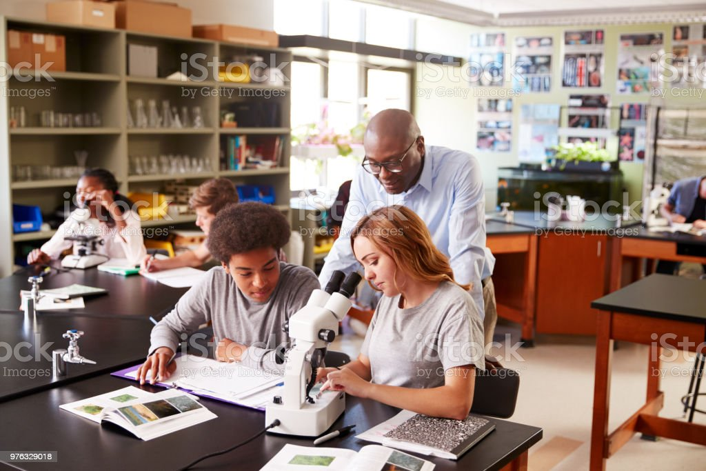 High School Students With Tutor Using Microscope In Biology Class stock photo