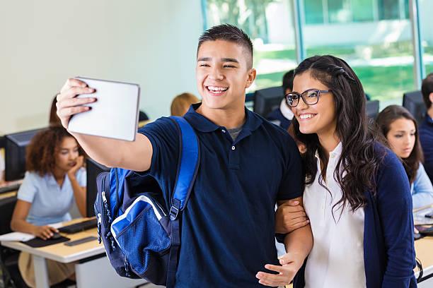 high school sweethearts prendendo selfie photo in laboratorio informatico - compagni scuola foto e immagini stock