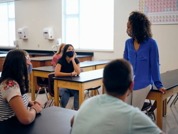 High School Teacher and Students In Classroom Wearing Protective Face Mask stock photo