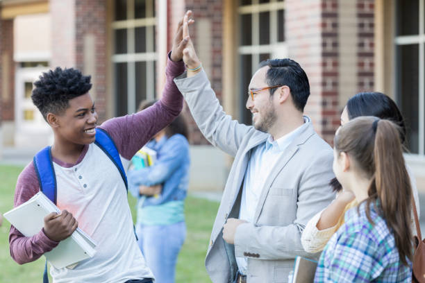high school teacher gives student a high five - high school teacher stock pictures, royalty-free photos & images