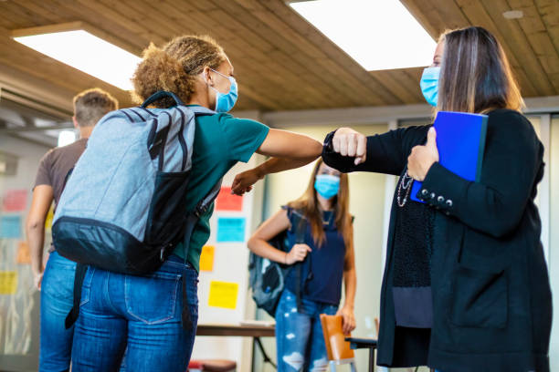 High School Teacher Greeting Student with Elbow Bump and all Wearing Face Masks in Classroom Setting stock photo
