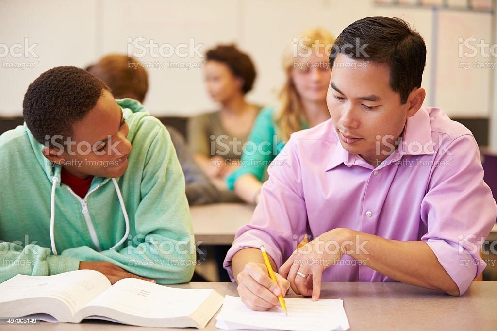High School Teacher Helping Student With Written Work stock photo