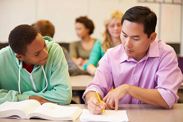 High School-Lehrer helfen Schüler mit schriftlichen Arbeiten – Foto