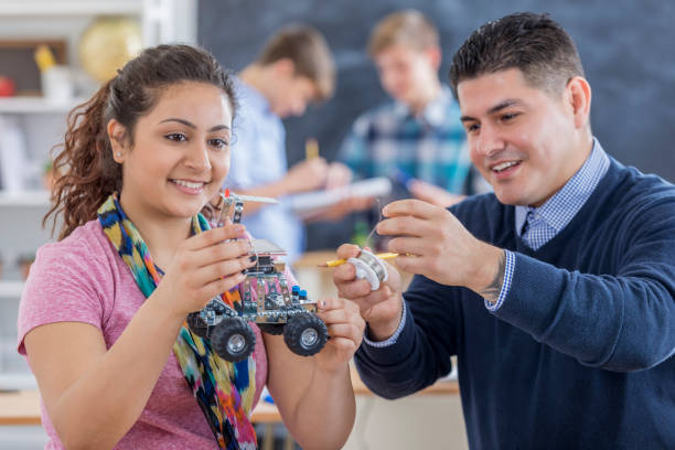 High school teacher helps student build robot stock photo