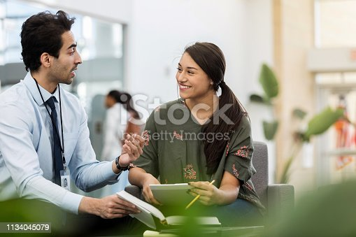 Confident mid adult male high school teacher gestures while helping a teenage girl with a homework assignment.