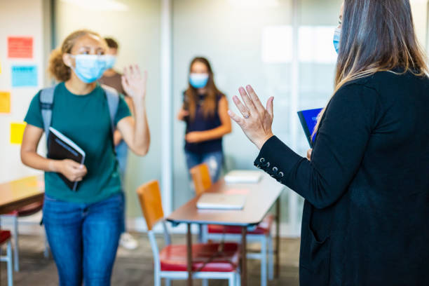High School Teacher Waving Goodbye to Female Student and all Wearing Face Masks in Classroom Setting with students in Background stock photo