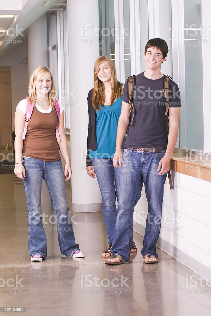 High school teenage friends in hallway walking and chatting royalty-free stock photo