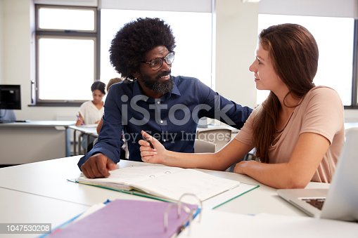 istock High School Tutor Giving Female Student One To One Tuition At Desk  In Classroom 1047530208