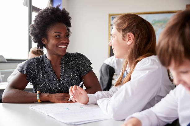 High School Tutor Giving Female Student Wearing Uniform One To One Tuition At Desk High School Tutor Giving Female Student Wearing Uniform One To One Tuition At Desk high school teacher stock pictures, royalty-free photos & images