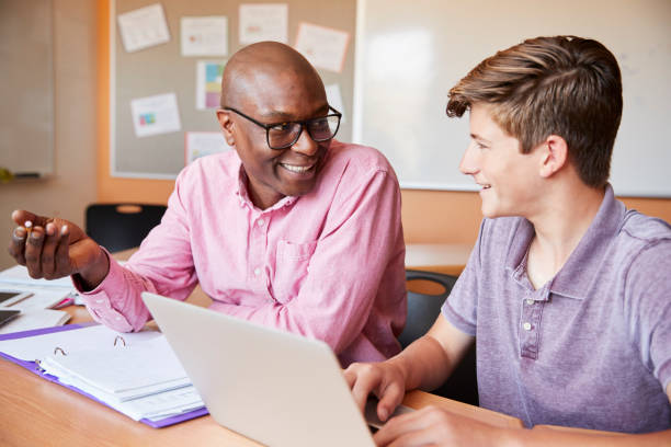 high school tutor giving male student one to one tuition at desk - high school teacher stock pictures, royalty-free photos & images