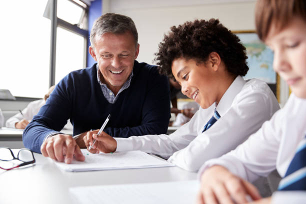 High School Tutor Giving Male Student Wearing Uniform One To One Tuition At Desk High School Tutor Giving Male Student Wearing Uniform One To One Tuition At Desk teacher stock pictures, royalty-free photos & images