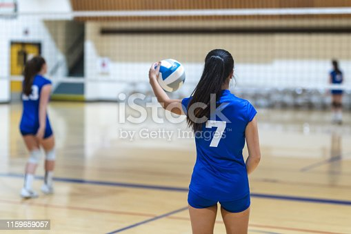 A high school volleyball player gets ready to serve during a game. The shot is from behind her.