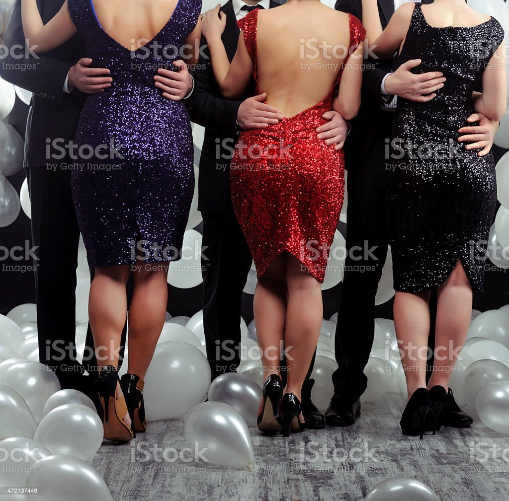 three fashion couples , woman in sequin dressed and man embracing...
