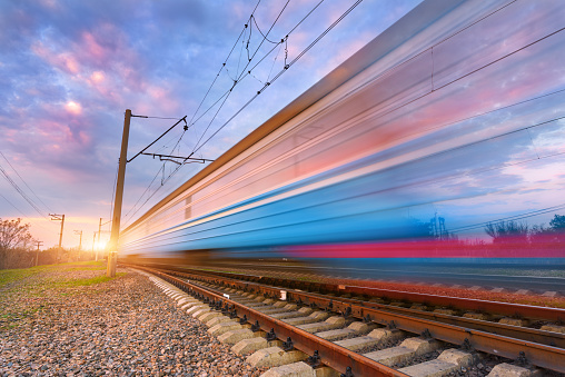High speed blue passenger train in motion on railroad at sunset. Blurred commuter train. Railway station against colorful sunny sky. Railroad travel, railway tourism. Industrial landscape. Concept