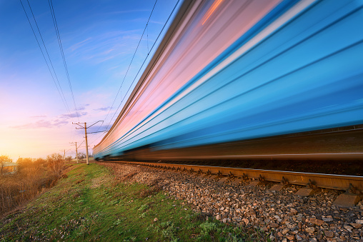 High speed blue passenger train in motion on railroad at sunset. Blurred commuter train. Railway station against colorful sky. Railroad travel, railway tourism. Rural industrial landscape. Concept