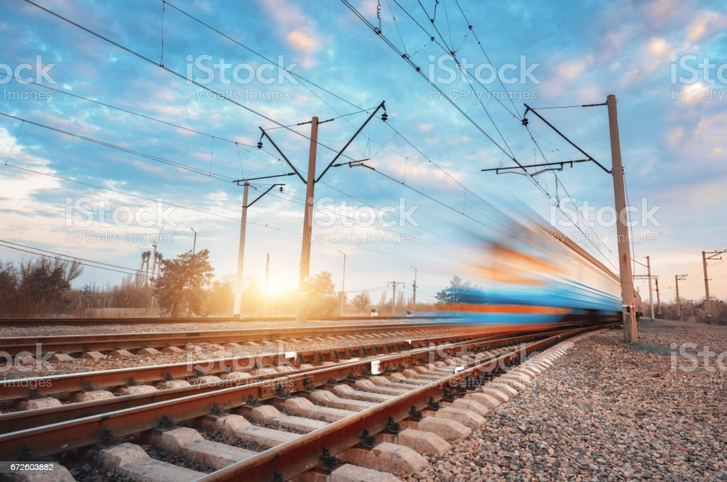 High speed blue passenger train in motion on railroad at sunset. Blurred commuter train. Railway station against colorful sky. Railroad travel, railway tourism. Rural industrial landscape. Vintage stock photo