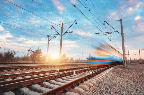 high speed blue passenger train in motion on railroad at sunset. blurred commuter train. railway station against colorful sky. railroad travel, railway tourism. rural industrial landscape. vintage - rail stock photos and pictures