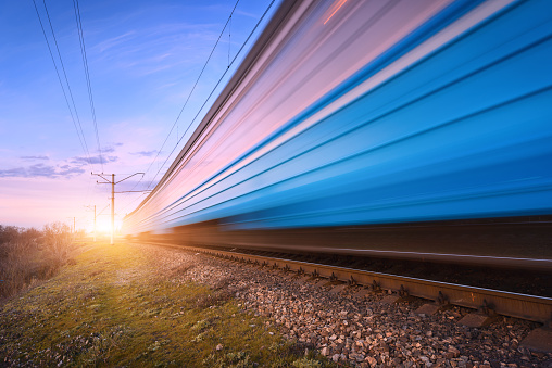 High speed blue passenger train in motion on railroad at sunset. Blurred modern commuter train. Railway station and colorful sky. Railroad travel, railway tourism. Rural industrial landscape in dusk.