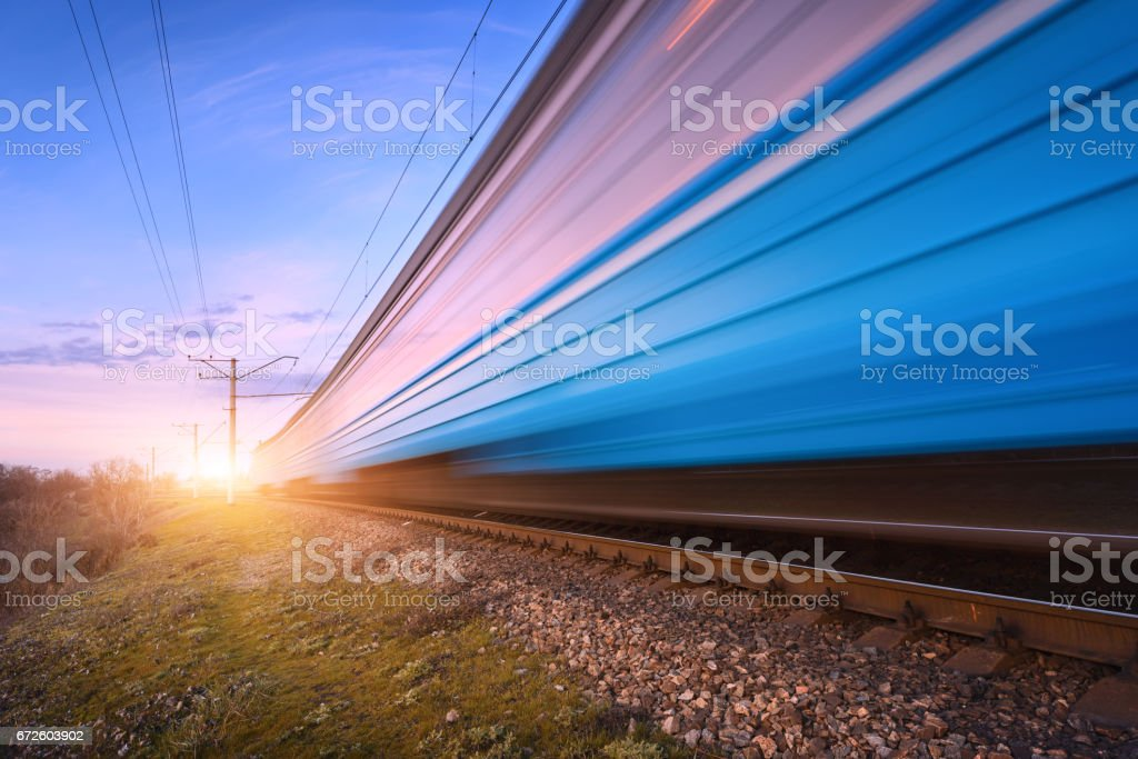 High speed blue passenger train in motion on railroad at sunset. Blurred modern commuter train. Railway station and colorful sky. Railroad travel, railway tourism. Rural industrial landscape in dusk. stock photo