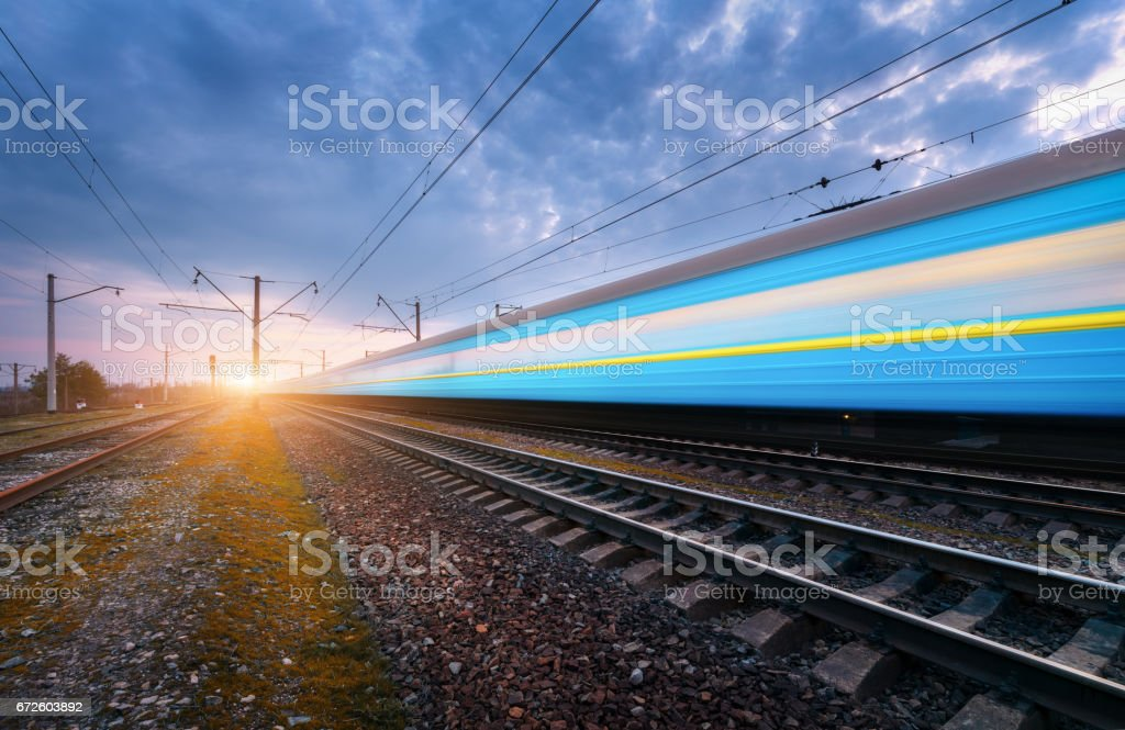 High speed blue passenger train in motion on railroad track at sunset. Blurred modern train. Railway station against dramatic cloudy sky. Railroad travel, railway tourism. Rural industrial landscape stock photo