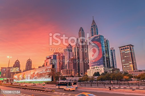 27 November 2019, UAE, Dubai: High speed highway road at sunset among high skyscrapers in downtown of Dubai city