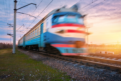 High speed passenger electric train in motion on railroad at sunset. Blurred old commuter train. Railway station against blue sky. Railroad travel, railway tourism. Rural industrial landscape. Concept