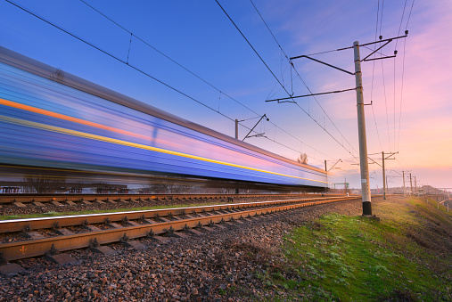 High speed passenger train in motion on railroad at sunset. Blurred commuter train. Railway station against colorful blue sky. Railroad travel, railway tourism. Rural industrial landscape. Concept