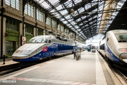 Paris, France - July 12, 2013: High speed TGV trains parked at the Gare de Lyon train station with passengers walking on the platform between the trains.