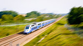 A TGV high speed train driving at full speed in the french countryside.