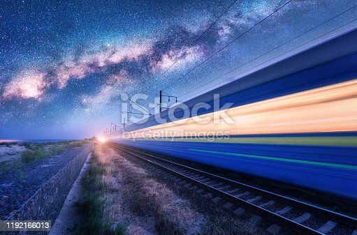 istock High speed train in motion and Milky Way at starry night. Industrial landscape with sky and stars over blurred modern passenger train and railroad. Railway station and space. Technology and nature 1192166013