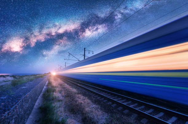 High speed train in motion and Milky Way at starry night. Industrial landscape with sky and stars over blurred modern passenger train and railroad. Railway station and space. Technology and nature stock photo