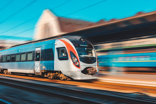 High speed train in motion at the railway station at sunset in Europe. Modern intercity train on the railway platform with motion blur effect. Industrial scene. Passenger transportation on railroad